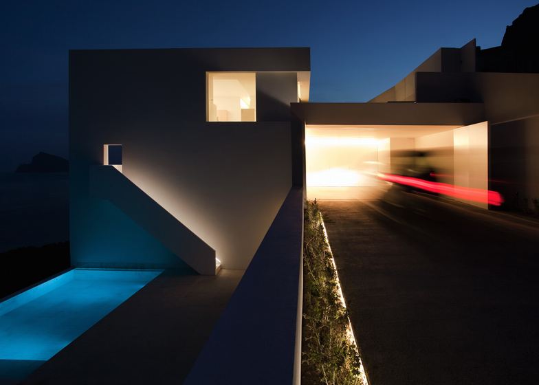 simple beautiful facade at night Monolithic-Volume-–-Cliff-View-Modern-White-House-in-Alicante-by-Fran-Silvestre-Arquitectos