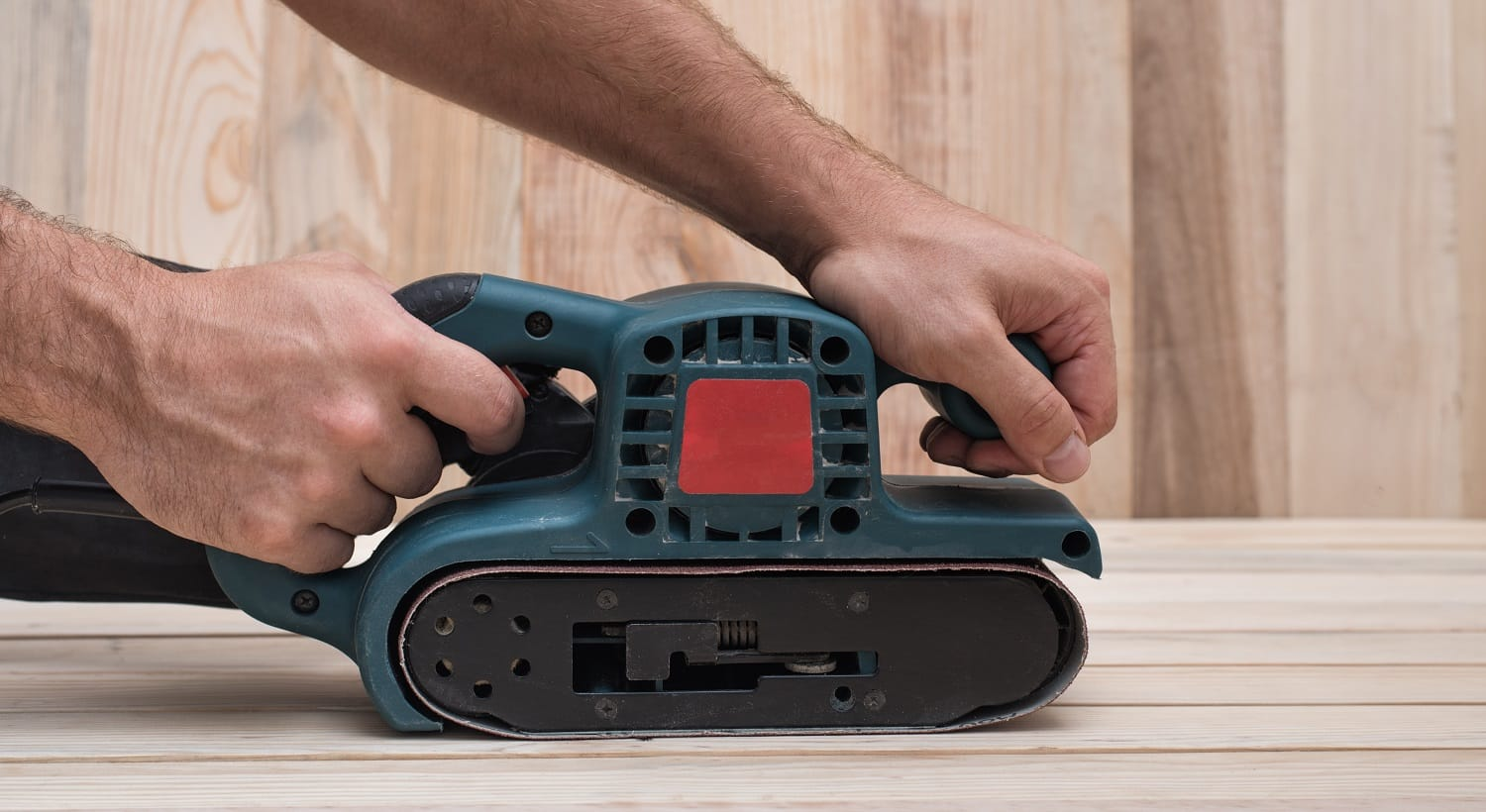 Electric belt sander, sanding machine in male hand. Processing of workpiece on light brown wooden table. Side view, close up