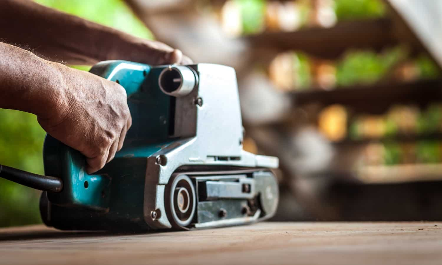 A skilled carpenter is using the power sander as a tool to polish his furniture instead of sandpaper.