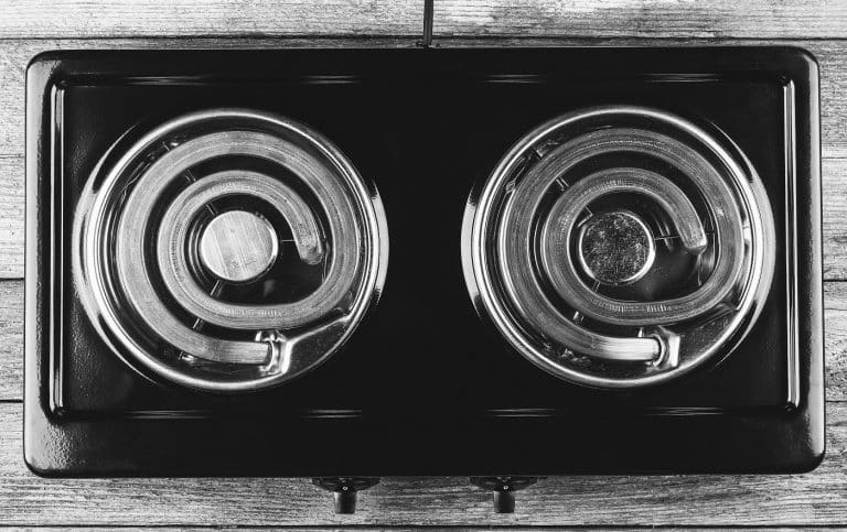 electric stove with two electric forks on a wooden table, top view close-up, black and white photo