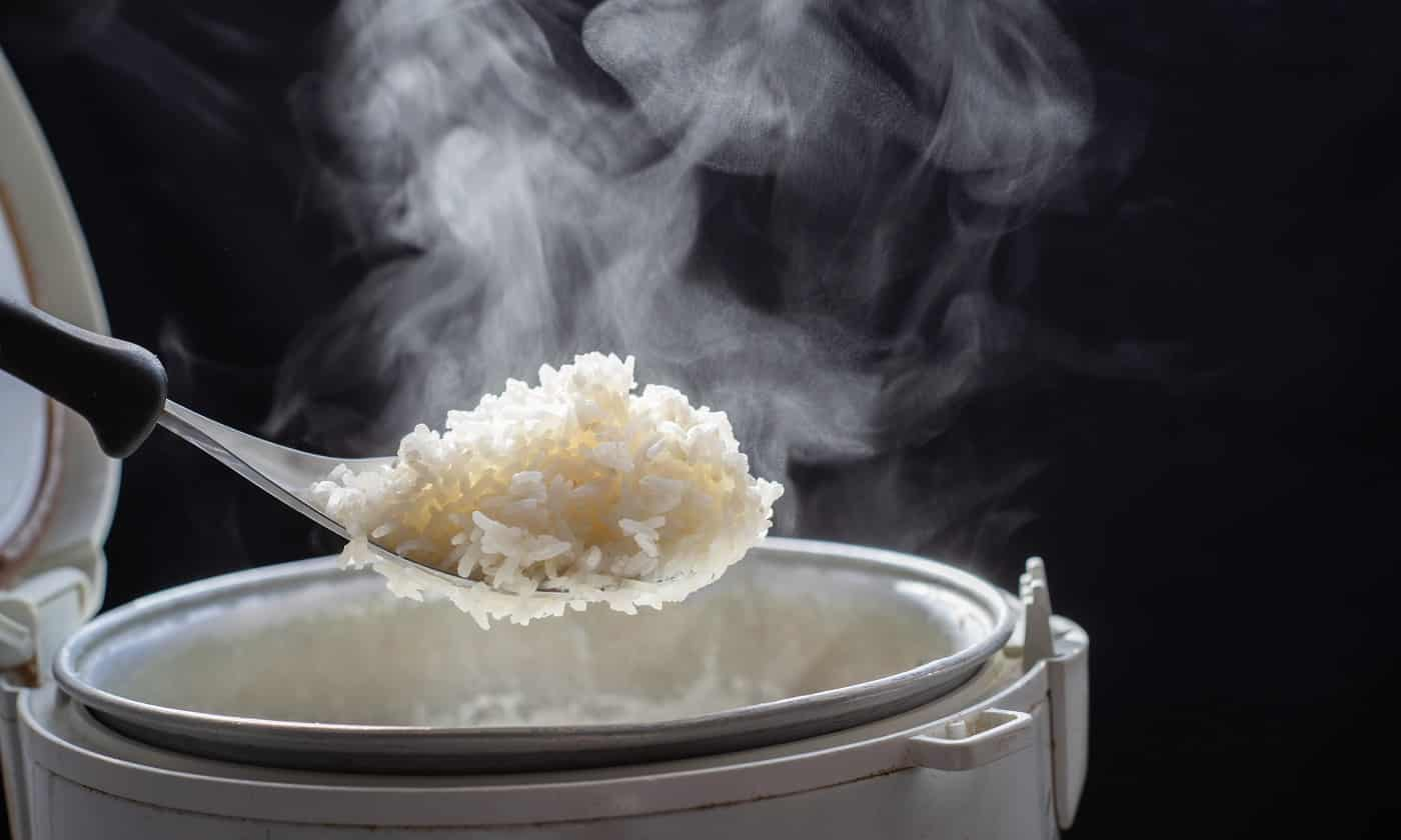 The steam from man taking tasty rice with spoon from cooker in kitchen, Jasmine rice cooking in electric rice cooker with steam. Selective Focus,
