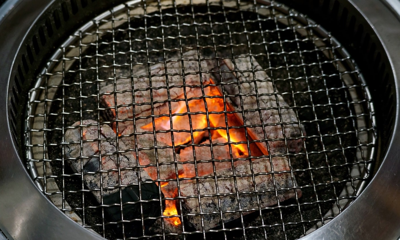 close up of a charcoal grill and grilling basket.