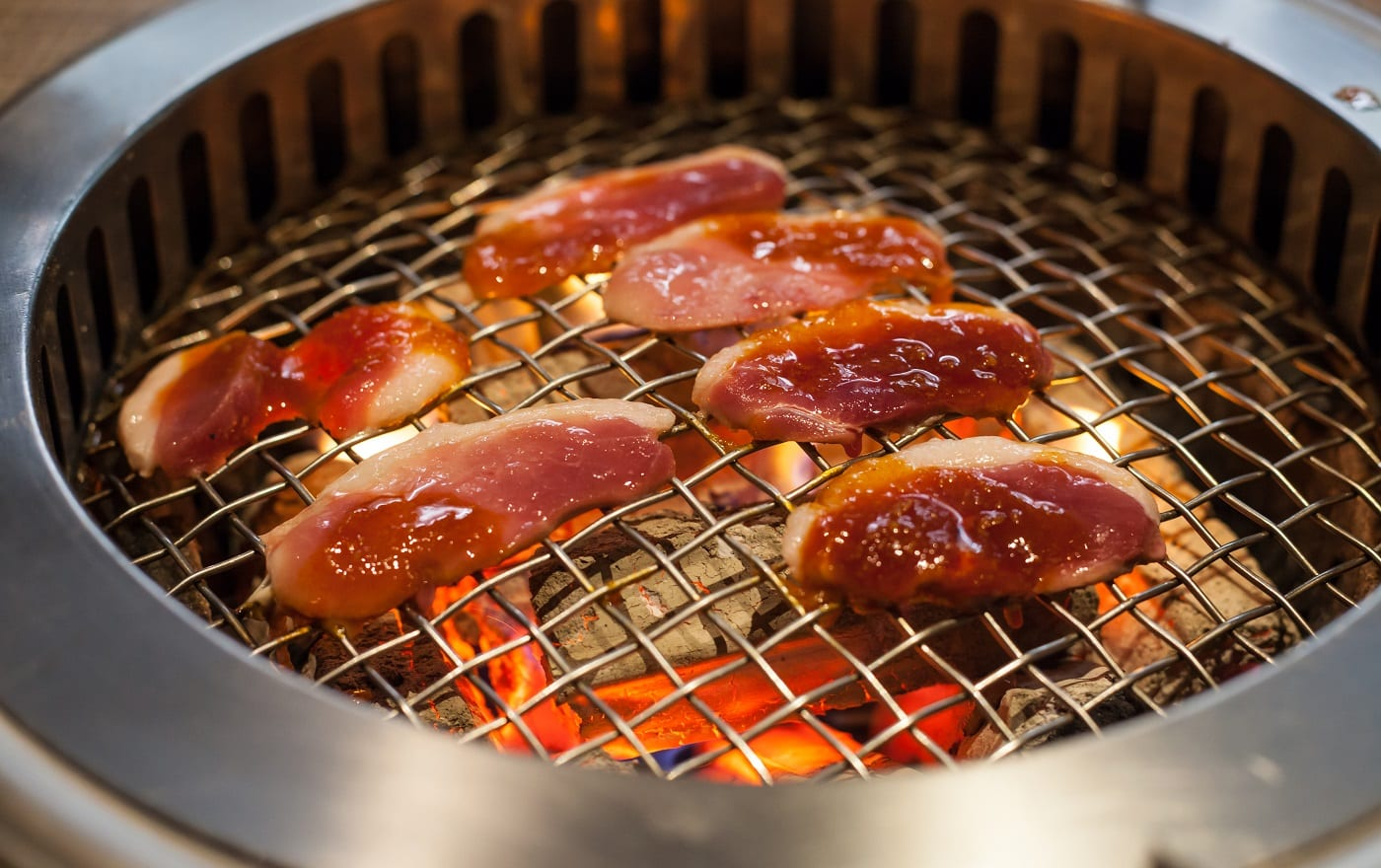 roasting duck meat and vegetable food on Glowing and Flaming hot natural wood charcoal lump frying mesh pan in food restaurant BBQ grill stove background.